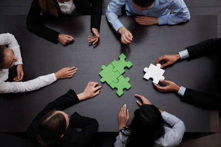 business team solving puzzle together