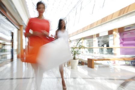 plaza comercial: Mujer caminando rápido en centro comercial con bolsas Foto de archivo