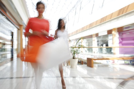Women walking fast in shopping mall with bags Stockfoto