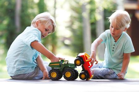 hermanos jugando: dos hermanos que juegan al aire libre con los coches de juguete
