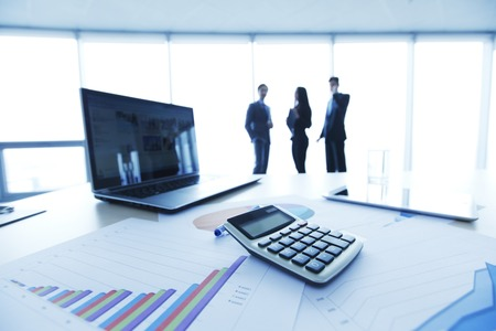 calculadora: Informes financieros, la calculadora y el ordenador portátil sobre la mesa en la oficina