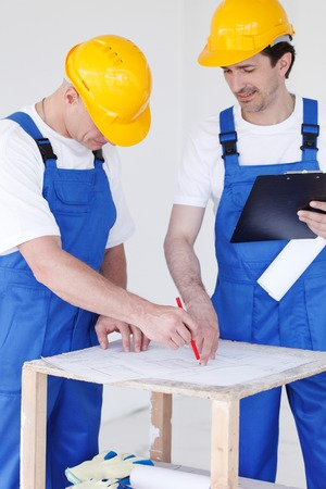 correcting: Two workers correcting a construction plan