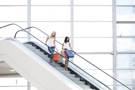 centro comercial: Mujeres felices hermosas jovenes en las escaleras mecánicas del centro comercial