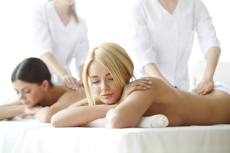 Two beautiful women getting massage in spa