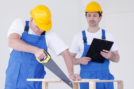 protective workwear: Two workmen in protective workwear with saw and folder