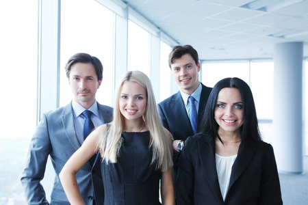 businesswoman suit: Happy business team of coworkers in office Stock Photo