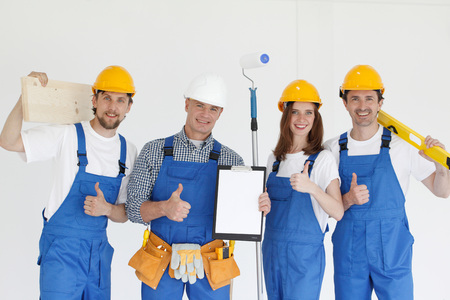 young worker: Group of smiling builders in hardhats with tools indoors Stock Photo