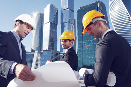 construction site helmet: Architects with blueprint looking at skyscreapers