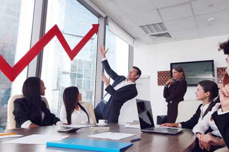 Business people discuss red arrow of income growth at meeting Stock Photo