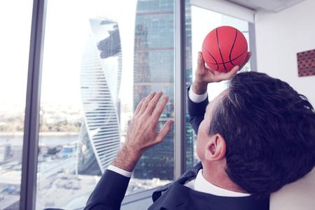 ejecutivo en oficina: Hombre de negocios jugando con una pelota de baloncesto en la oficina de