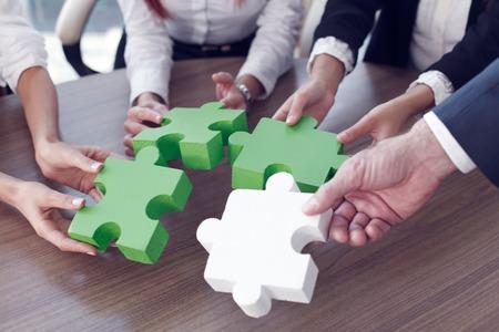 ジグソー パズルとオフィスで表すチーム サポートとヘルプの概念を組み立てるビジネス人々 のグループ 写真素材