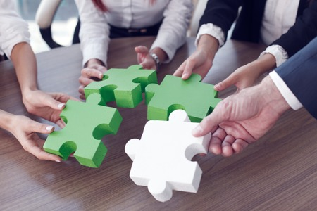 partnerships: Group of business people assembling jigsaw puzzle and represent team support and help concept in office Stock Photo