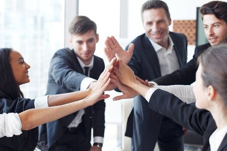 working group: Happy business team making high five with their hands in the office