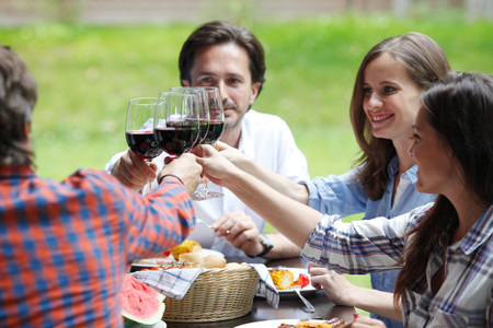clink: Friends clink glasses of red wine at outdoor dinner Stock Photo
