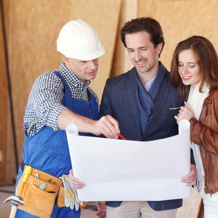 home plans: Construction: Young Couple Look At Home Plans with Builder Stock Photo