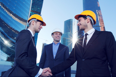 building industry: Investor and contractor shaking hands, view from below