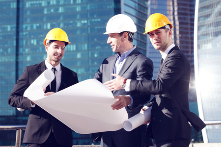worker construction: Architects with blueprint at skyscrapers background