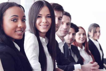 young: Business people sitting in a row and working, focus on pretty woman Stock Photo