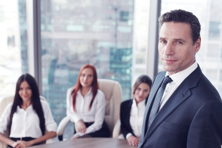 confidently: Group portrait of a professional business man and team looking confidently at camera