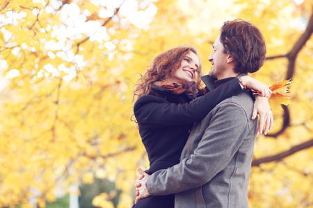 couple nature: Smiling couple hugging in autumn park on yellow maple tree background Stock Photo