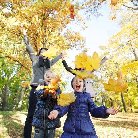 ni�os jugando: Familia feliz jugando con el arce hojas de oto�o en el parque Foto de archivo