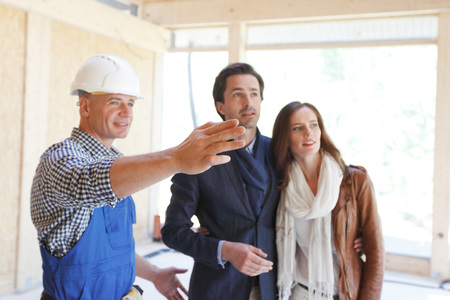 Worker in workwear shows new house to a couple