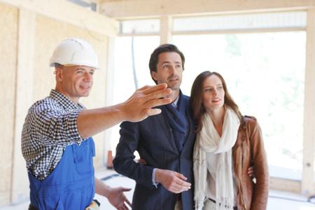 pareja en casa: Trabajador en la ropa de trabajo muestra nueva casa a una pareja