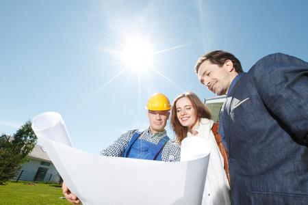 albañil: capataz muestra los planes de diseño casa a una joven pareja al aire libre