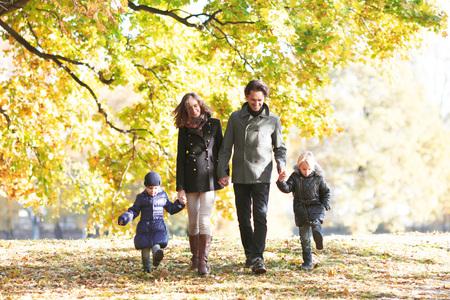秋の公園で歩いている子供を持つ家族の肖像画