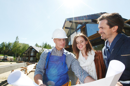 Worker shows construction plan to young couple outside house under construction