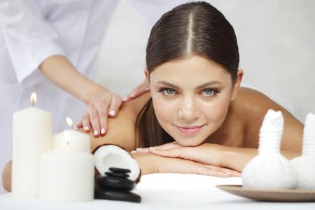 massaggio: Bella giovane donna che ottiene massaggio termale vicino Archivio Fotografico