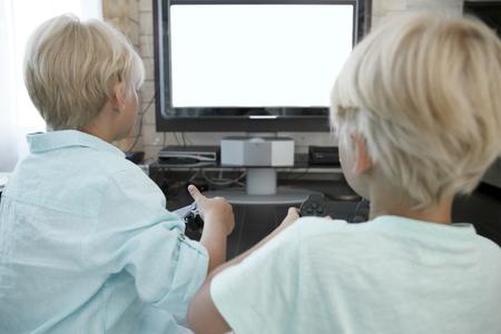 jugando videojuegos: Dos hermanos jugando juegos de video en casa
