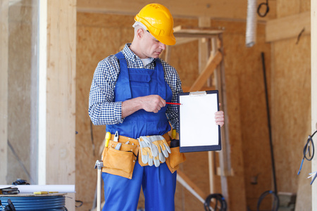 foreman: Construction foreman wearing a yellow safety helmet holding a clipboard Stock Photo
