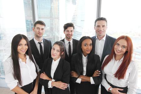 高層ビルでビューとオフィスで男性と女性のビジネス チームの肖像画 写真素材