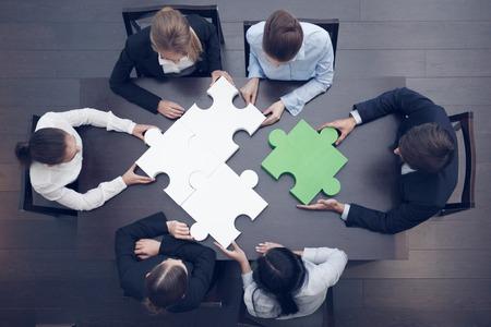 Skupina podnikatelů sestavování puzzle, podporu týmu a pomoc koncepce
