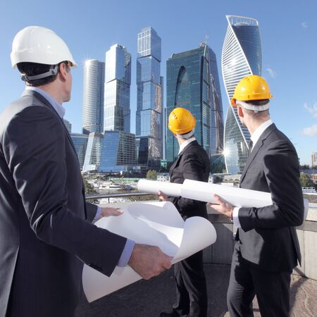 construction work: Architects with blueprint at skyscrapers background