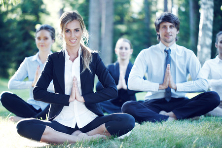 Business people practicing yoga in park Stock Photo