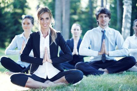 mujer meditando: La gente de negocios que practican yoga en el parque