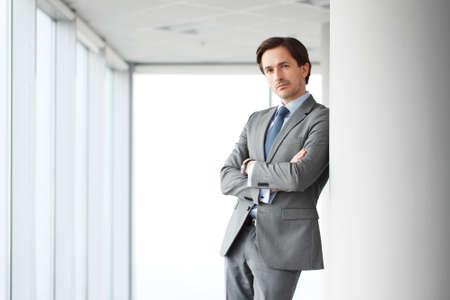guy portrait: Portrait of handsome businessman standing near windows in office