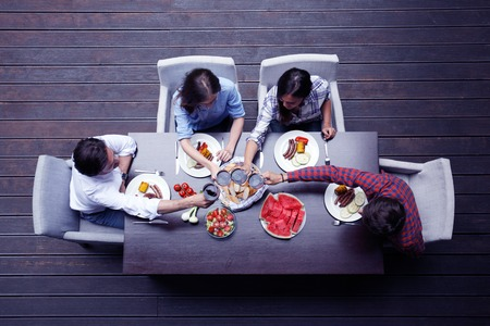 frankfurter: Four friends having dinner, top view
