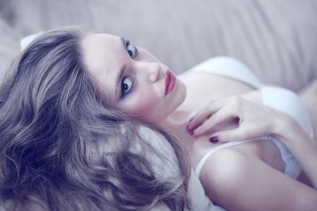 ソファーに下着姿の美しい若い女性の肖像画 写真素材