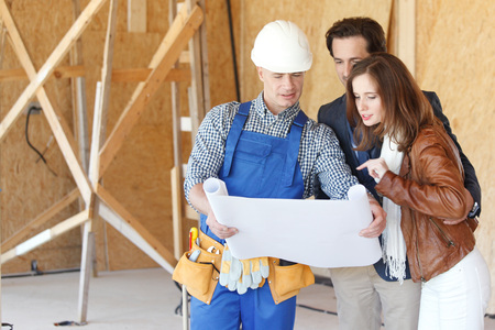 Foreman shows house design plans to a young couple