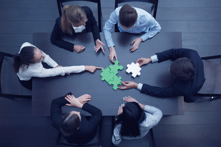 Group of business people assembling jigsaw puzzle, team support and help concept