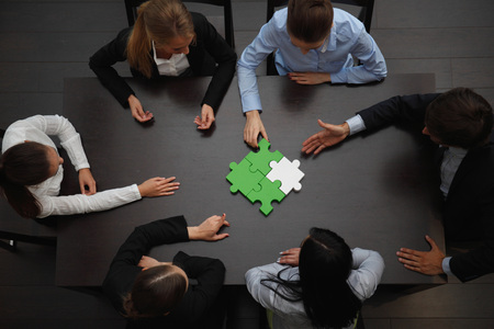 business help: Group of business people assembling jigsaw puzzle, team support and help concept