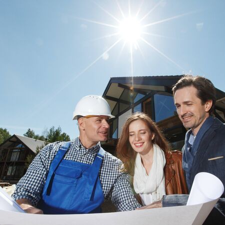 site: Worker shows house design plans to a young couple outdoors