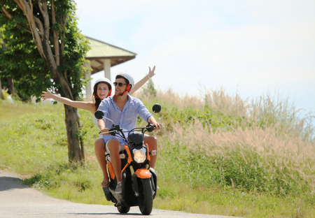 Happy couple on a scooter at summer vacation Stock Photo