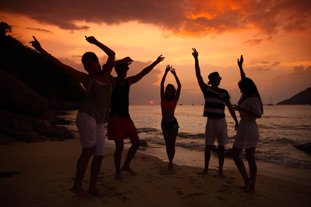 people partying: Group of people partying on beach at sunset