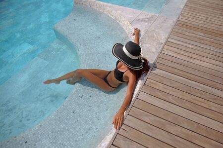 femme brune sexy: Beautiful woman relaxing at swimming pool at tourist resort