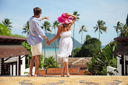 luxuries: Young couple look at tourist resort and sea Stock Photo