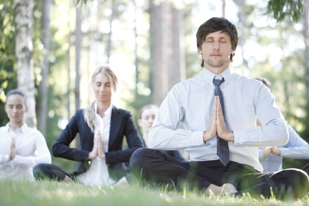 executive women: Business people practicing yoga in park Stock Photo